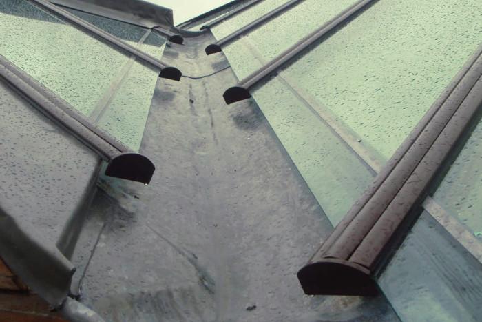Conductos de evacuación de agua de lluvia sobre un tejado de cristal